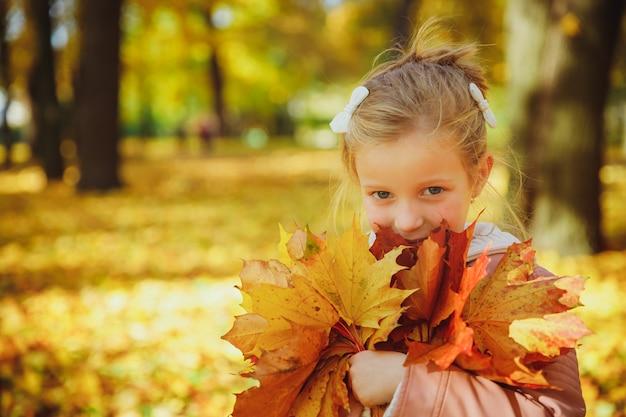 秋の肖像画。フォレスト内の黄色の葉で遊んで面白い少女。秋の公園で散歩の子。黄金の秋。幼児の女の子、紅葉の花束を持つ肖像画