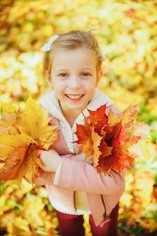 かわいい巻き毛の少女の秋の肖像画。フォレスト内の黄色の葉で遊んで面白い少女。黄金の秋。幼児の女の子、紅葉の花束を持つ肖像画