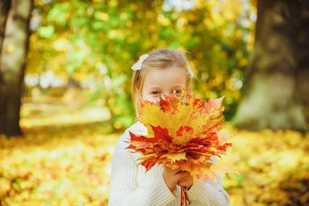 かわいい巻き毛の少女の秋の肖像画。フォレスト内の黄色の葉で遊んで面白い少女。秋の公園で子。秋の葉の花束