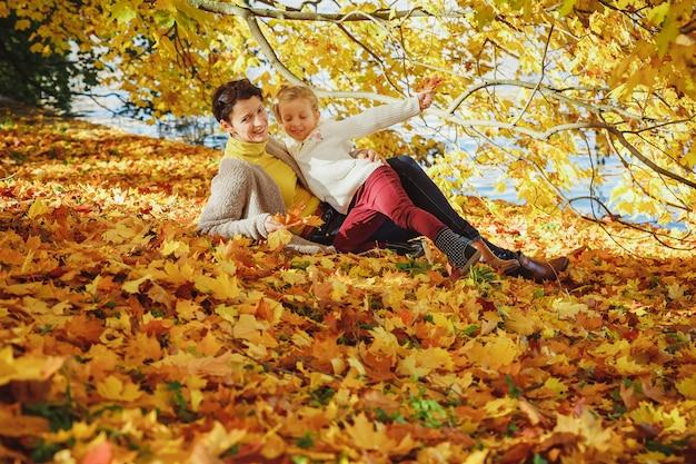秋の公園で娘と遊ぶ母。ママと彼女の子供が屋外で一緒に遊ぶ。楽しんで幸せな愛情のある家族。スタイリッシュな母と子が着ます。