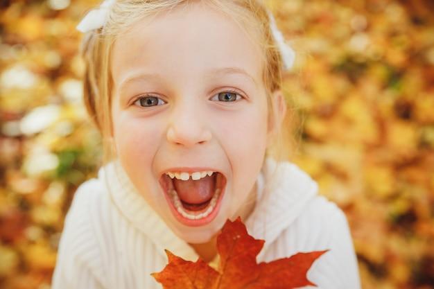 秋と遊ぶ幸せな少女を残します。秋の公園で口を開けて面白い女の子。感情的な顔をだまして顔を作ると素敵な女の子。子供の笑顔と笑い。