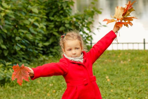 子供はカエデの葉と踊っています。