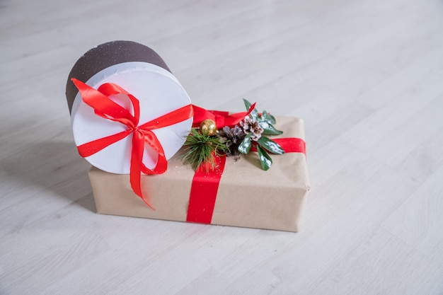Подарки на рождество на деревянной предпосылке. обернутые подарки. подарки в ремесле и цветной бумаге украшены красной лентой луки и снежинки.
