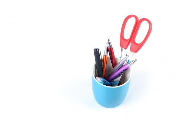 カラフルなペンとオレンジ色のはさみは分離された青いマグカップ