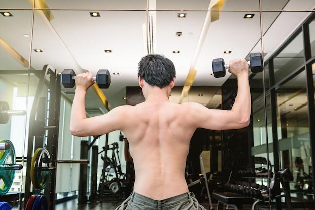 フィットネス男性は、ダンベルを持ち上げてトレーニングや運動をしています。スポーツジムのフィットネスルームで。