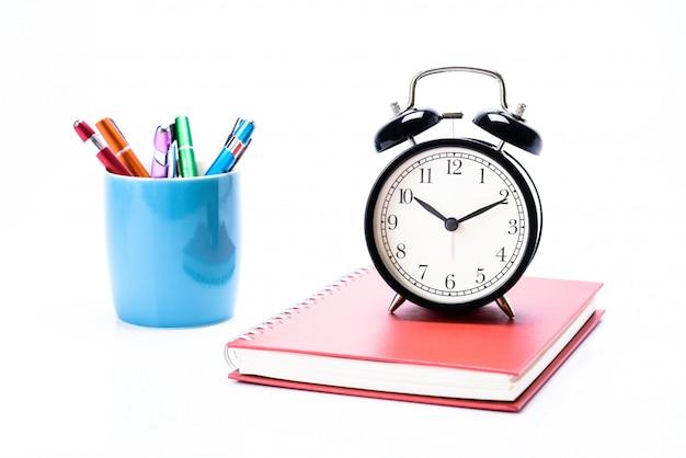 コンセプト教育またはビジネス:カラフルなペンで赤い本に置かれた黒い目覚まし時計は、青いマグカップに置かれます。
