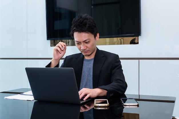 Концепция бизнеса в офисе: азиатский молодой бизнесмен с ноутбуком и мобильным телефоном