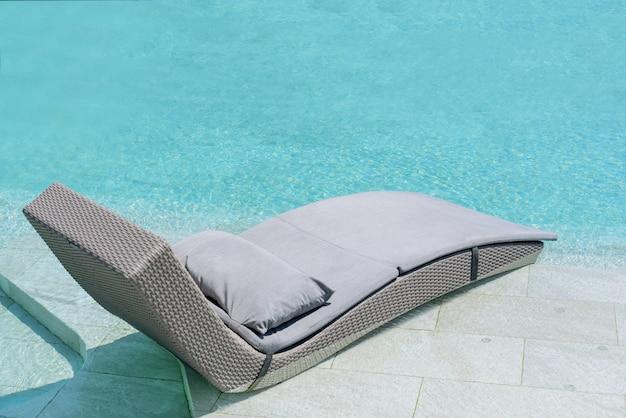 Расслабляющая или отдыха кровать из ротанга в бассейне.