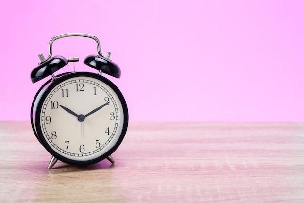 木製のテーブルに黒のレトロな目覚まし時計