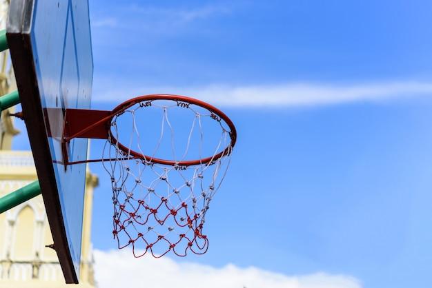 青い空と雲のバスケットボールのフープ