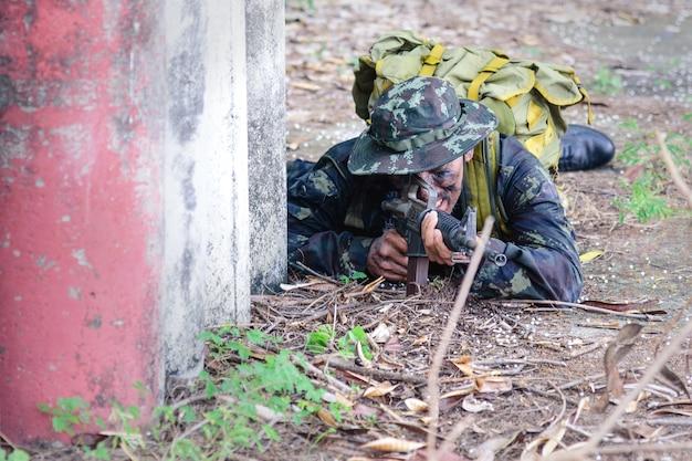 戦闘計画のシミュレーション。兵士または軍が芝生の上でしゃがんで、敵を待ち伏せするために機関銃を持っています。