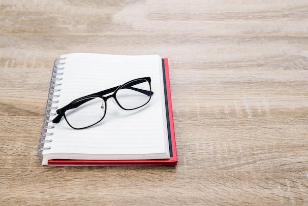 コンセプト教育またはビジネス:木製のテーブルに黒のメガネで日記やメモ帳を開きます。