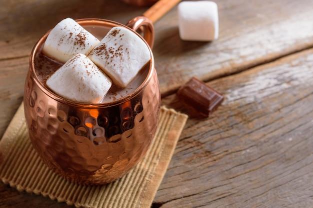 木製のテーブルに置かれた銅のコップにマシュマロと自家製ホットチョコレート。