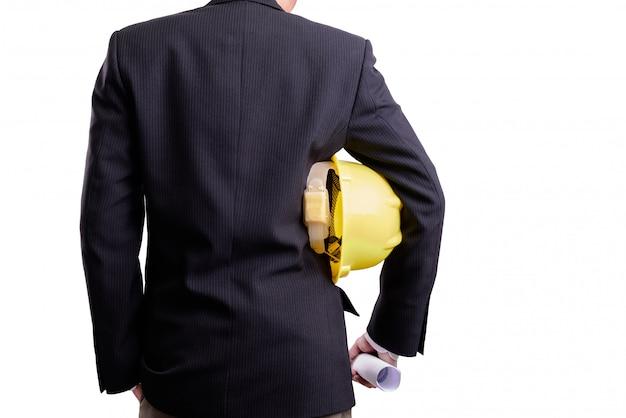 ビジネスコンセプト:白い壁に分離された安全ヘルメットを持つビジネス男の後ろ。