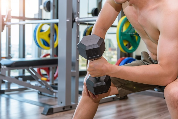 フィットネス男は、ダンベルを持ち上げてトレーニングや運動をしています。スポーツジムのフィットネスルームで。
