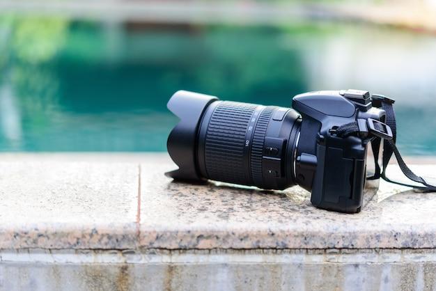 スイミングプールの端に置かれた黒いデジタル一眼レフカメラ。