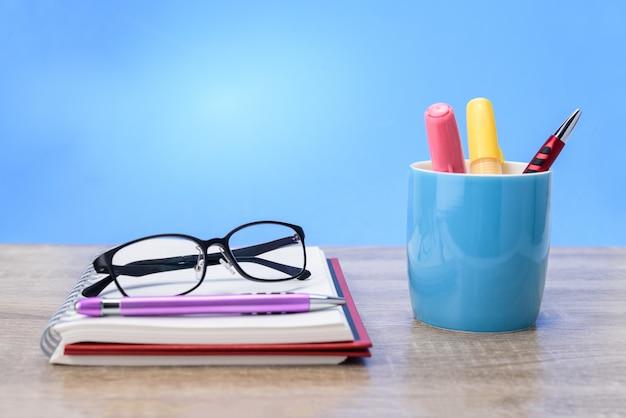 メガネと紫のペンは青いマグカップでカラフルなペンで赤い本に配置