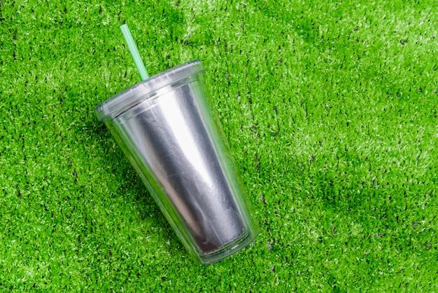 Вид сверху пластиковый стакан с соломой или трубкой на зеленой траве