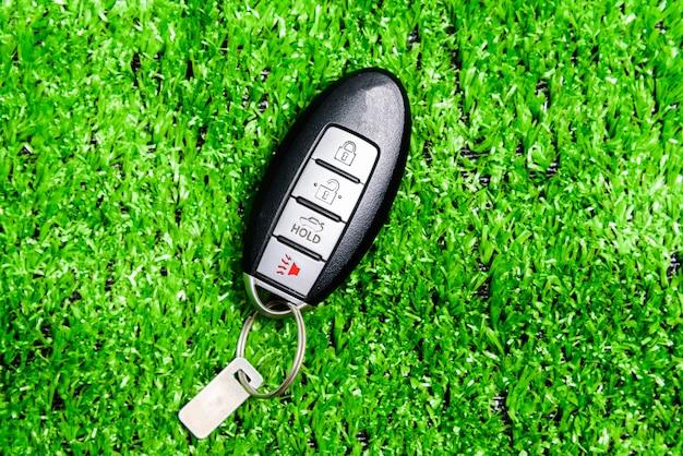 Авто пульт для блокировки или разблокировки двери автомобиля, изолированные на зеленой траве