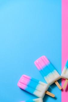青とピンクのパステル調の背景にフルーツアイスクリームスティック、アイスキャンディー、アイスポップまたは冷凍庫