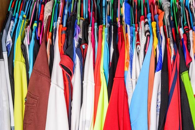 カラフルなシャツや服がクローゼットの中に掛けられています。