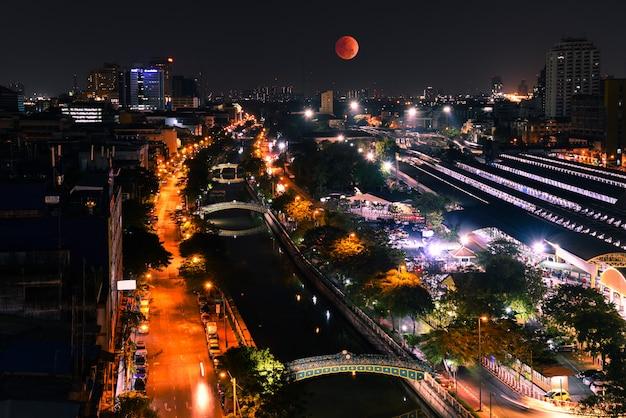 Супер кровавая луна в небе. с высоким углом зрения бангкок ночью.