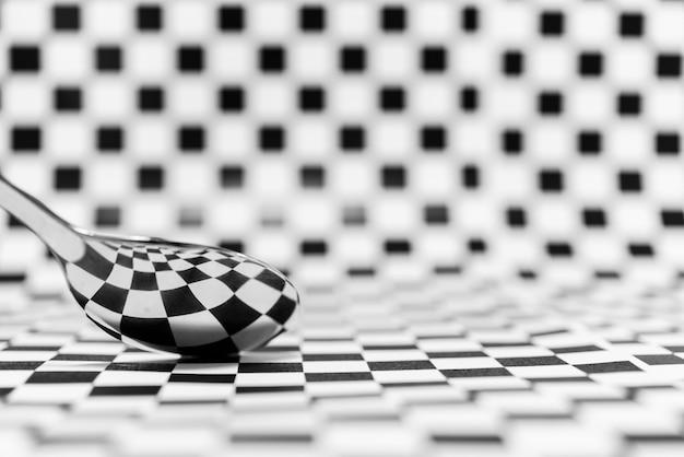 抽象的な幾何学的な白黒または市松模様の大理石の背景のスプーンの反射
