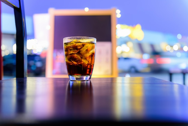 夜のボケ味を持つテーブルの上のガラスの水のソーダまたはコーラを輝く