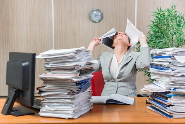 Женщина в состоянии стресса от чрезмерной бумажной работы
