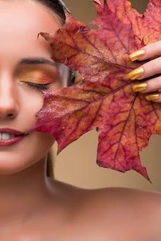 秋の乾燥葉の中で美しい女性