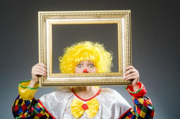 Клоун в смешной концепции на темном фоне