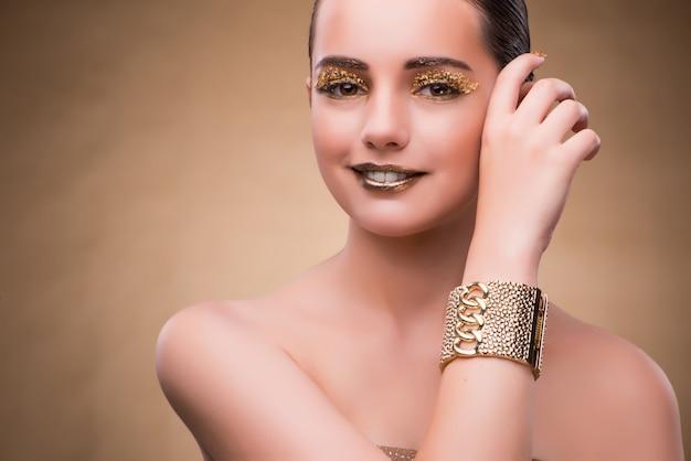 Женщина с золотым браслетом в концепции красоты