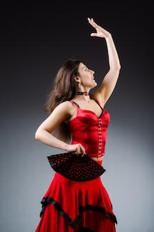 踊りのファンを持つ女性