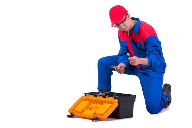 白で隔離されるレンチスパナを持つ若い修理工