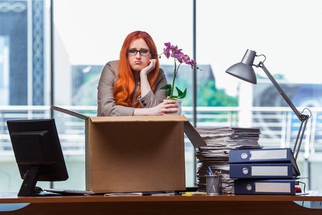 Рыжая женщина переезжает в новый офис, собирая вещи