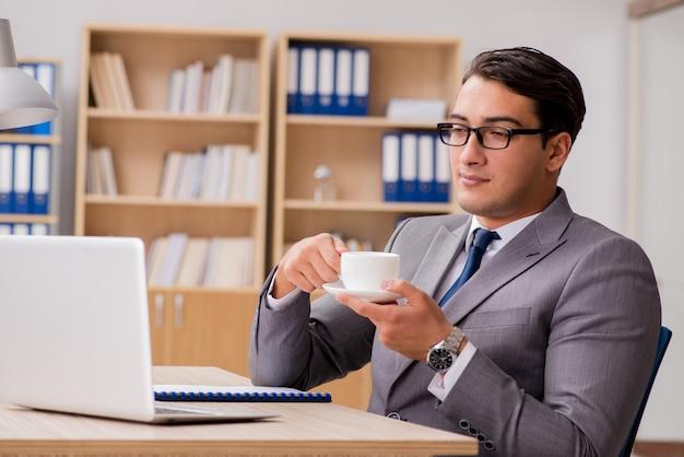 オフィスで働く若いハンサムなビジネスマン