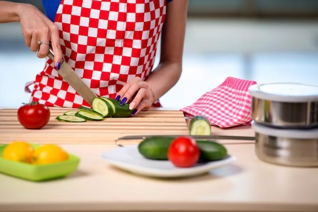 女性が台所でサラダを準備します。