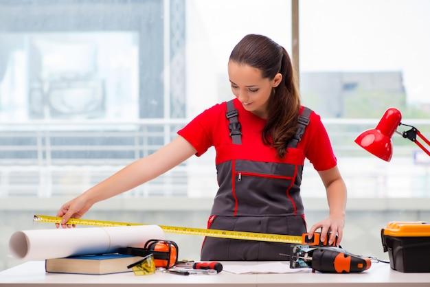 Молодая женщина в комбинезоне делает ремонт