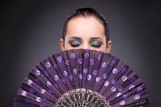 ファッションのコンセプトでファンを持つ美しい女性