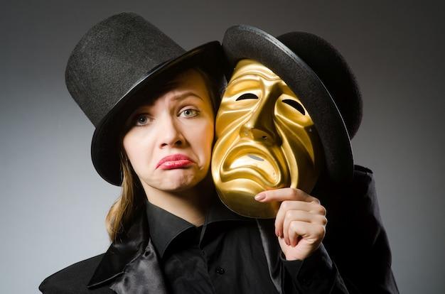 面白いコンセプトでマスクを持つ女性