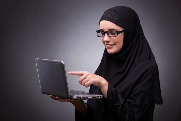 暗い背景に対して黒のドレスでイスラム教徒の女性