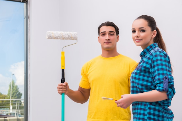Молодая пара красит стену дома