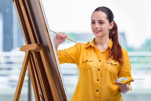 Молодой студент художник рисует картины в студии
