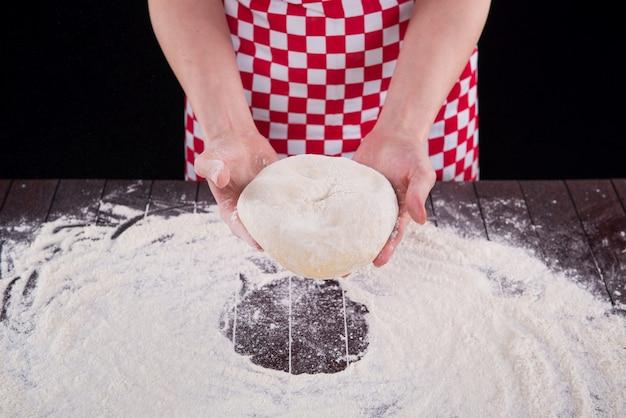 Повар готовит тесто для выпечки на кухне
