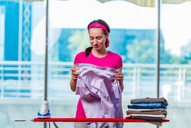 ボード上の服をアイロンの若い女性