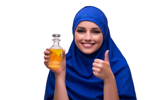 白で隔離される香水の瓶を持つアラビアの女性
