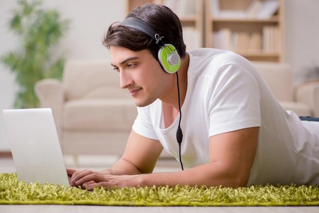 若い男がラップトップから音楽を聴く