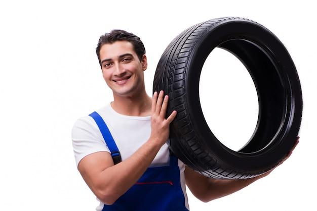 白で隔離されるハンサムなタイヤ修理