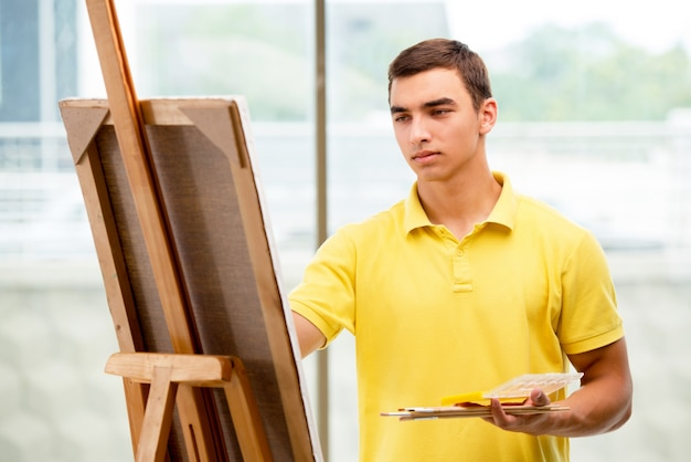 Молодой мужчина художник рисует картины в яркой студии