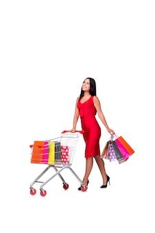 白で隔離されるショッピングの後の赤いドレスを着た女性